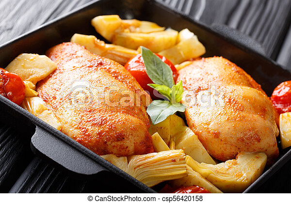 Spicy chicken breast with baked artichokes and tomatoes close-up on a plate. horizontal - csp56420158
