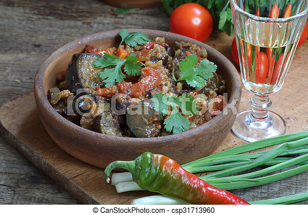 Spicy eggplants with tomatoes and pepper and a vodka wine-glass - csp31713960