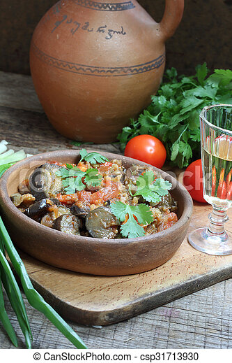 Spicy eggplants with tomatoes and pepper and a vodka wine-glass - csp31713930