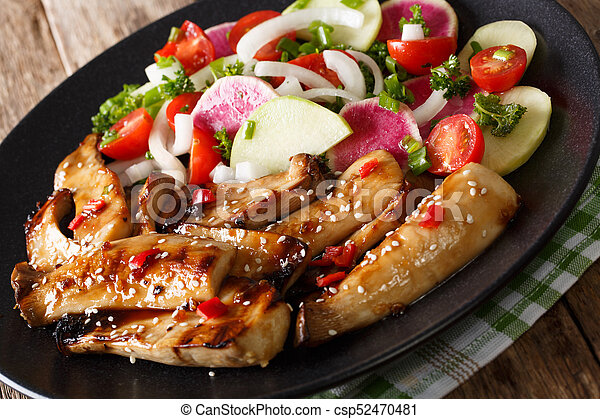 Spicy grilled king oyster mushrooms and a salad of radish and tomato close-up. horizontal - csp52470481