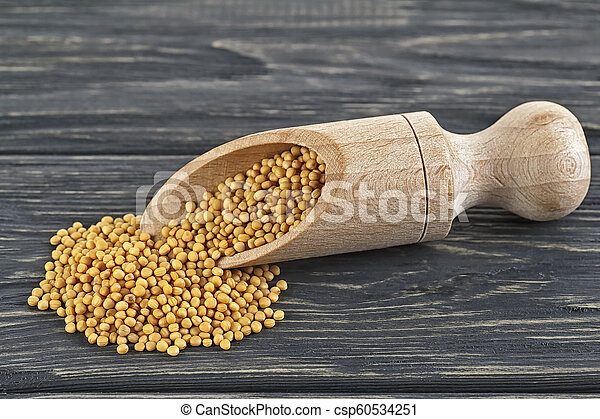 Spicy mustard seeds in wooden scoop, wooden background - csp60534251