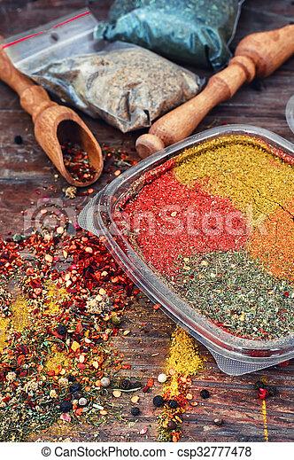 Spicy seasoning on wooden background - csp32777478