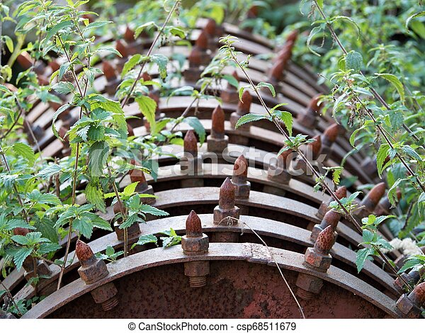 Spiky wheels for grass court mulching. Rusty steel machine - csp68511679