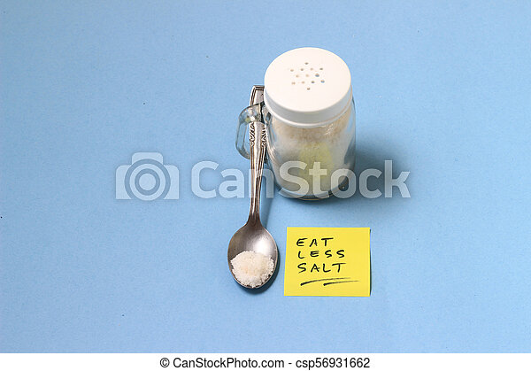 spilled salt from small shaker at blue paper background - csp56931662