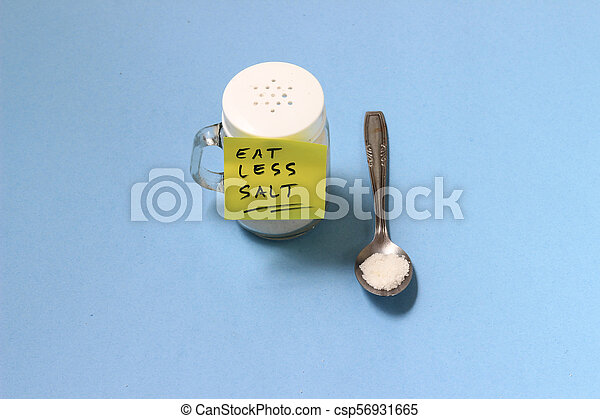 spilled salt from small shaker at blue paper background - csp56931665