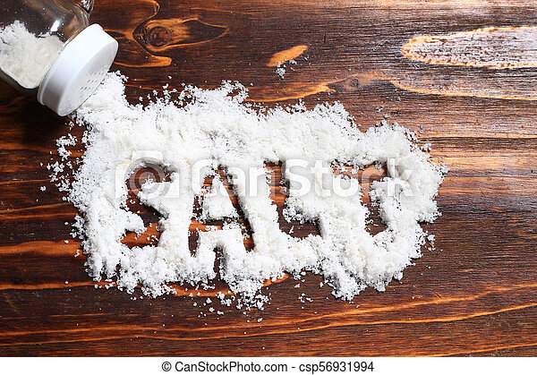 spilled salt from small shaker at wooden board background - csp56931994