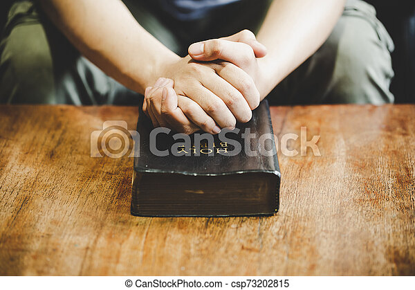 Spirituality and religion, Hands folded in prayer on a Holy Bible in church concept for faith. - csp73202815