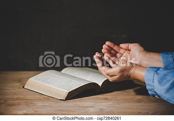 Spirituality and religion, Hands folded in prayer on a Holy Bible in church concept for faith. - csp72840261