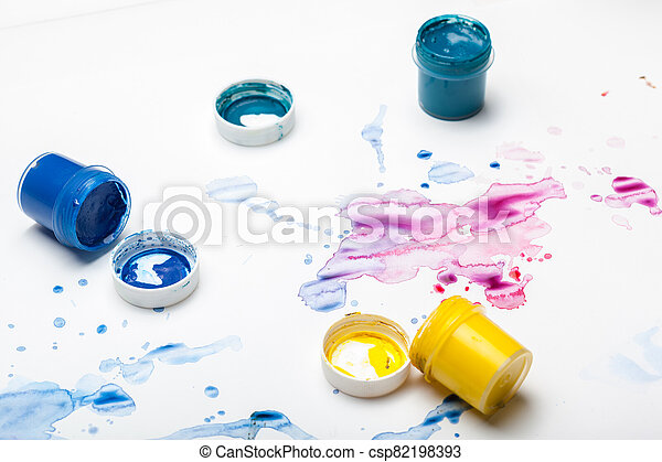splashes of watercolor paint and painting supplies close up - csp82198393
