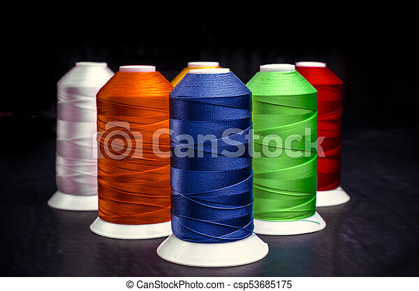 Spools of thread on a black background - csp53685175