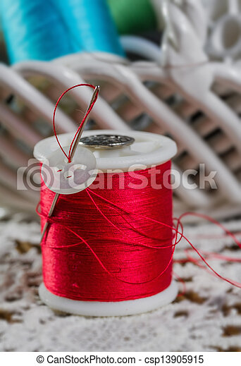 spools of thread on a wooden background - csp13905915