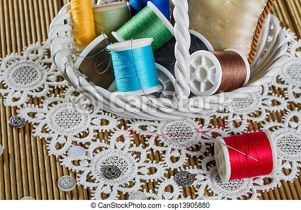 spools of thread on a wooden background - csp13905880