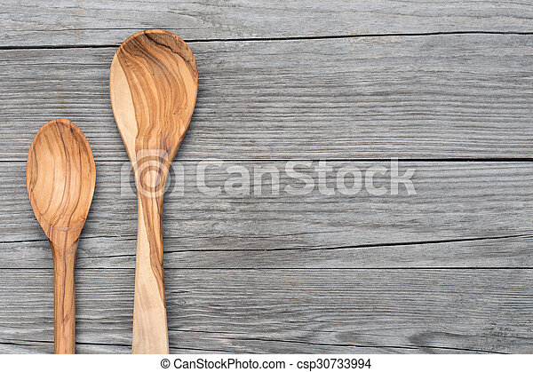 spoons of olive wood on grey table - csp30733994