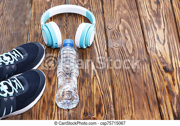Sports equipment. Sneakers, water and headphones on wooden background - csp75715067