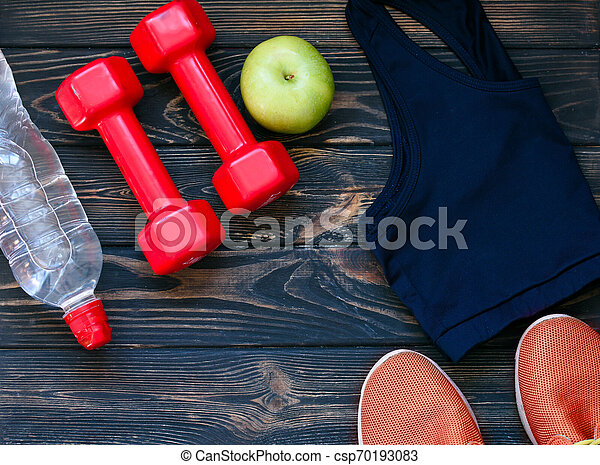 Sports sneakers, dumbbells, drinking clean water, on the background - csp70193083