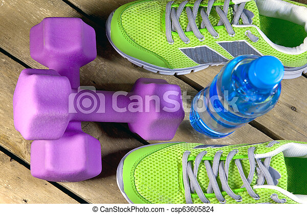 Sports sneakers, dumbbells, drinking water on a wooden background - csp63605824