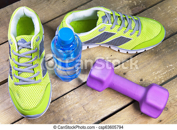 Sports sneakers, dumbbells, drinking water on a wooden background - csp63605794