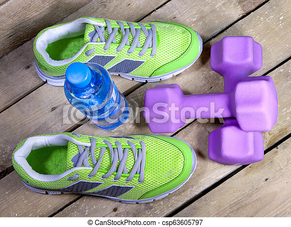 Sports sneakers, dumbbells, drinking water on a wooden background - csp63605797