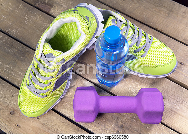 Sports sneakers, dumbbells, drinking water on a wooden background - csp63605801