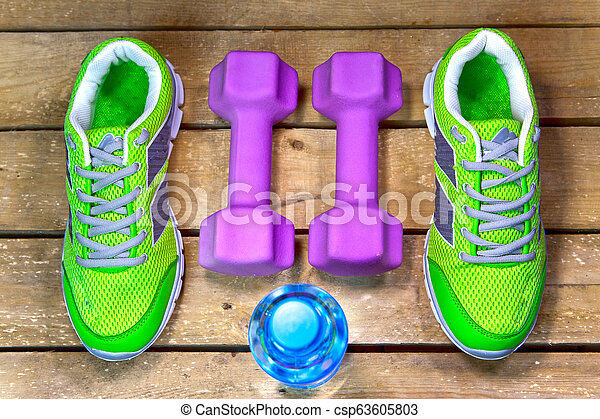 Sports sneakers, dumbbells, drinking water on a wooden background - csp63605803