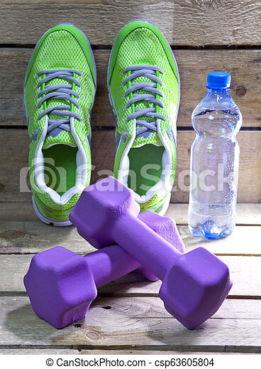 Sports sneakers, dumbbells, drinking water on a wooden background - csp63605804