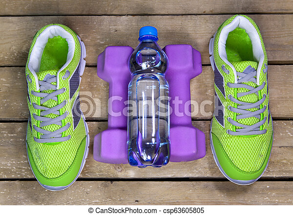 Sports sneakers, dumbbells, drinking water on a wooden background - csp63605805
