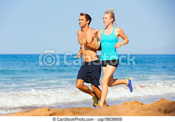 Sporty couple jogging together on the beach - csp18638959