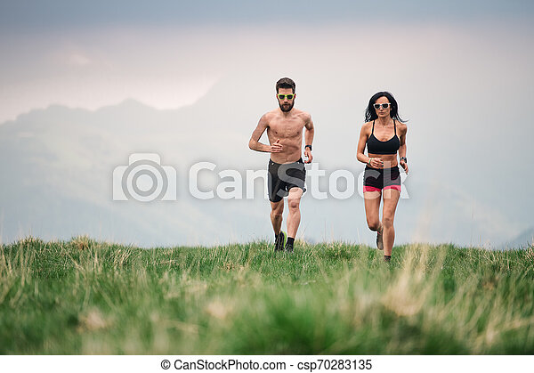 Sporty man and woman run hot in the summer on hill meadows - csp70283135