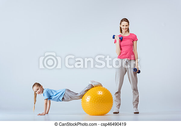 sporty mother with dumbbells and daughter with fitness ball excising together - csp46490419