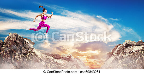 Sporty woman jump through the gap between hills over sky background. - csp69843251