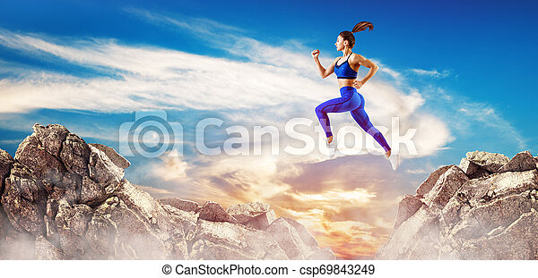 Sporty woman jump through the gap between hills over sky background. - csp69843249