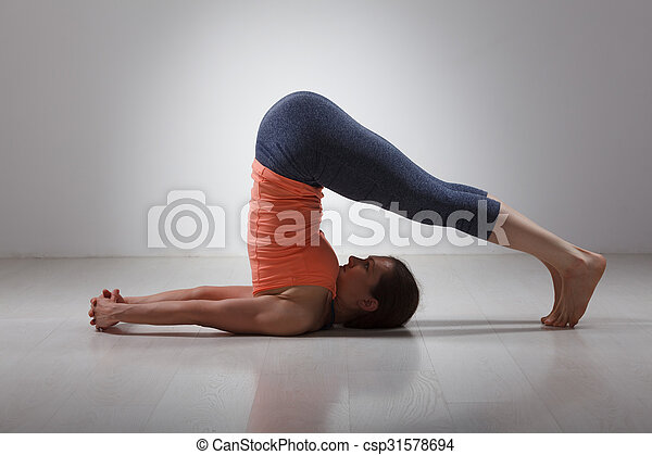 sporty woman practices yoga asana halasana beautiful