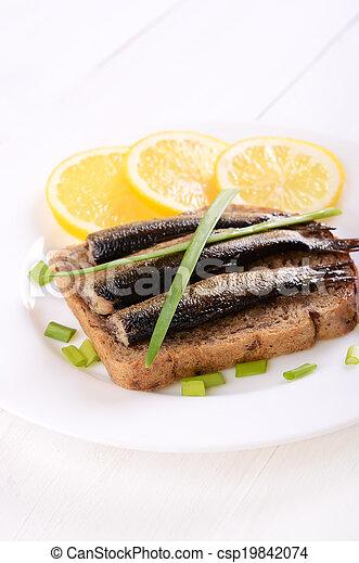 Sprats sandwich on white plate - csp19842074