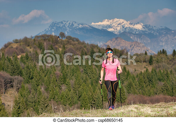 Spring in the mountains between green and snow. A lonely girl during a trek - csp68650145