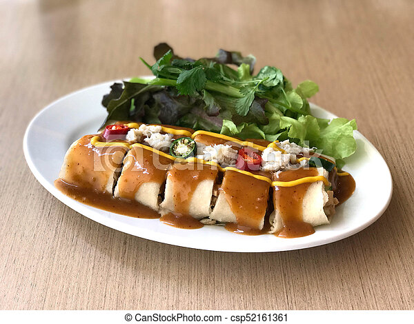 Spring roll with tamarind sauce topped with crab and mustard and chili - csp52161361