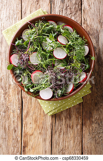 Spring salad of radish with microgreen mix close-up in a bowl. Vertical top view - csp68330459