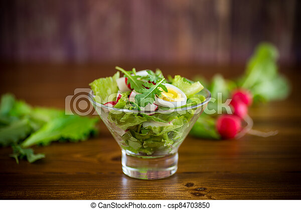 spring salad with arugula, boiled eggs, fresh radish, salad leaves in a glass bowl - csp84703850