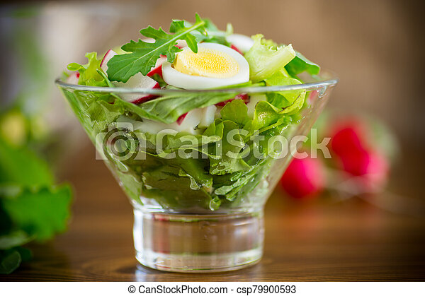 spring salad with arugula, boiled eggs, fresh radish, salad leaves in a glass bowl - csp79900593