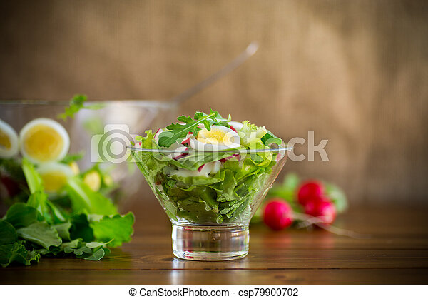 spring salad with arugula, boiled eggs, fresh radish, salad leaves in a glass bowl - csp79900702