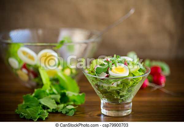spring salad with arugula, boiled eggs, fresh radish, salad leaves in a glass bowl - csp79900703