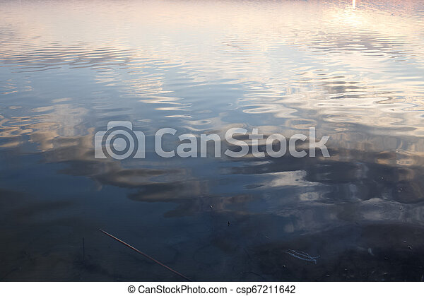 Spring sky reflection in water of lake. - csp67211642