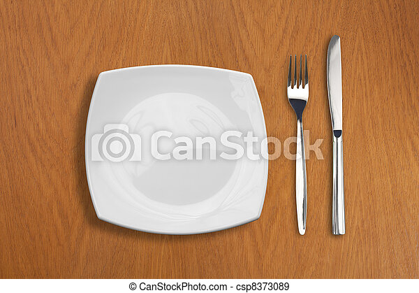 square white plate, knife and fork on wooden table - csp8373089