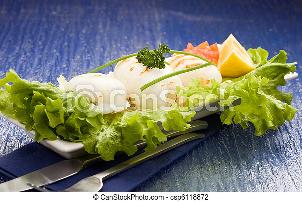 Squid with lettuce on blue glasstable - csp6118872
