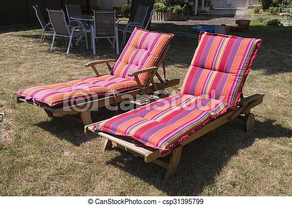 Zwei Liegestühle im sonnigen Garten - csp31395799