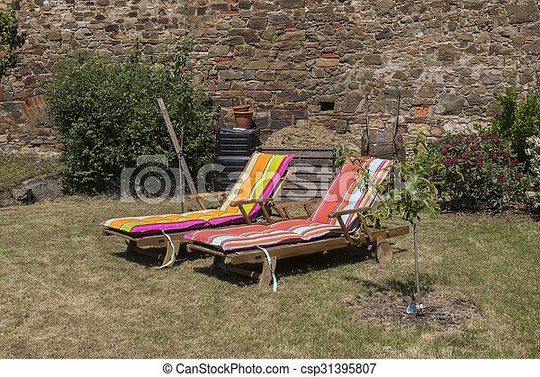 Zwei Liegestühle im sonnigen Garten - csp31395807