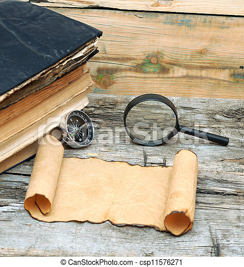 Stack of antique books with compass, magnifying glass and paper scroll on wood background - csp11576271