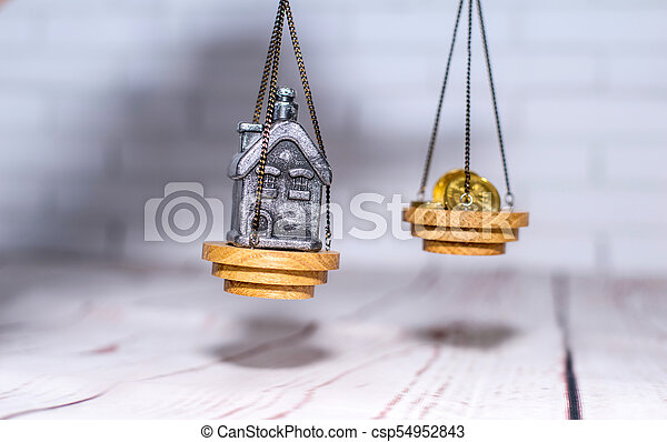 Stack of coins and a small house on the scales. The concept of choice, cash savings and purchase of real estate. - csp54952843