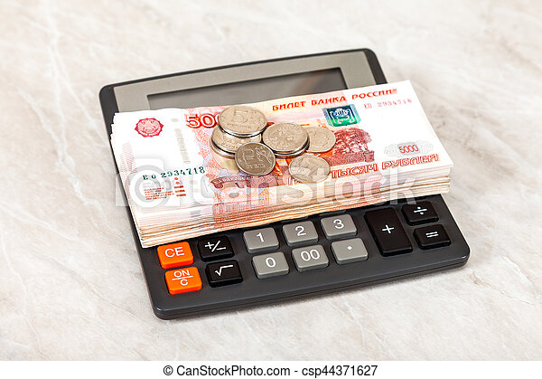 Stack of five thousandths banknotes of russian roubles, coins and calculator - csp44371627
