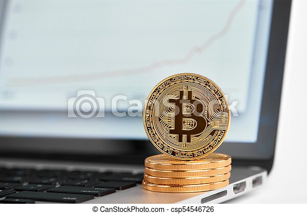 Stack of golden bitcoins with one bitcoin on its edge standing on laptop with financial chart on its screen - csp54546726