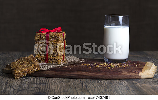 Stack of oatmeal crunchy cookies and milk in background - csp47407481